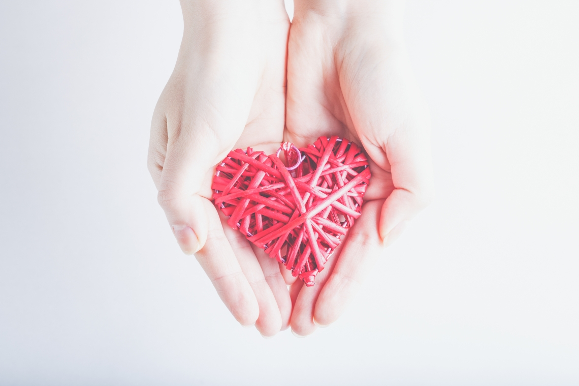 Female hands with a entwined vintage romantic red heart on a sno