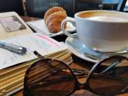 a table with a coffee cup, sunglasses, open journal with a pen laying on top of it and a croissant