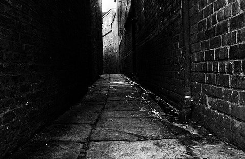 Empty street in black and white. Narrow alley with brick walls on both sides