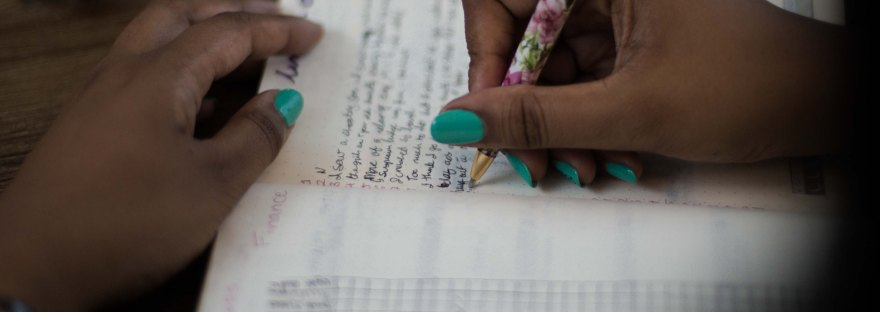 Hands writing on a bullet journal, coffee cup in upper right hand. Pens on table. Pen used to write with is floral.